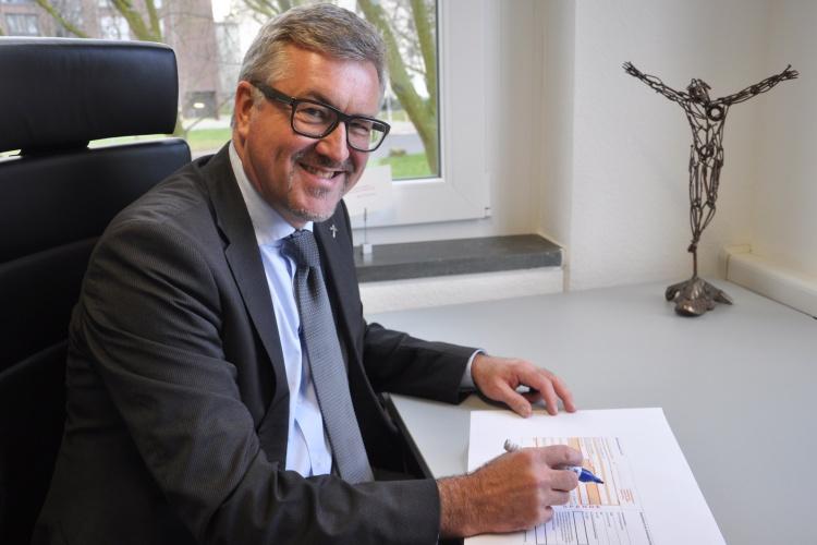 Diakonie RWL-Vorstand Christian Heine-Göttelmann füllt Überweisungsträger aus
