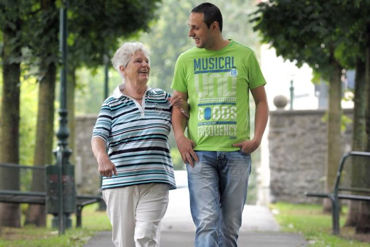 Spaziergang eines Mitarbeiters des diakonischen Alle Cafe Plus mit einer demenzell erkrankten Frau