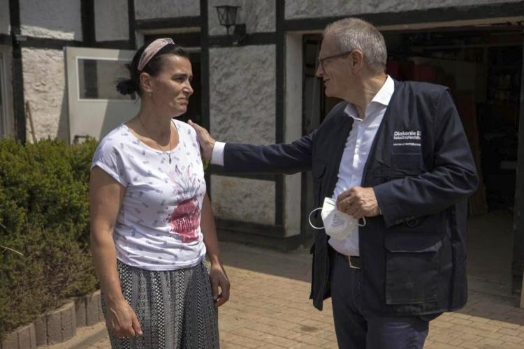 Diakonie-Präsident Ulrich Lilie tröstet eine vom Hochwasser betroffene Frau