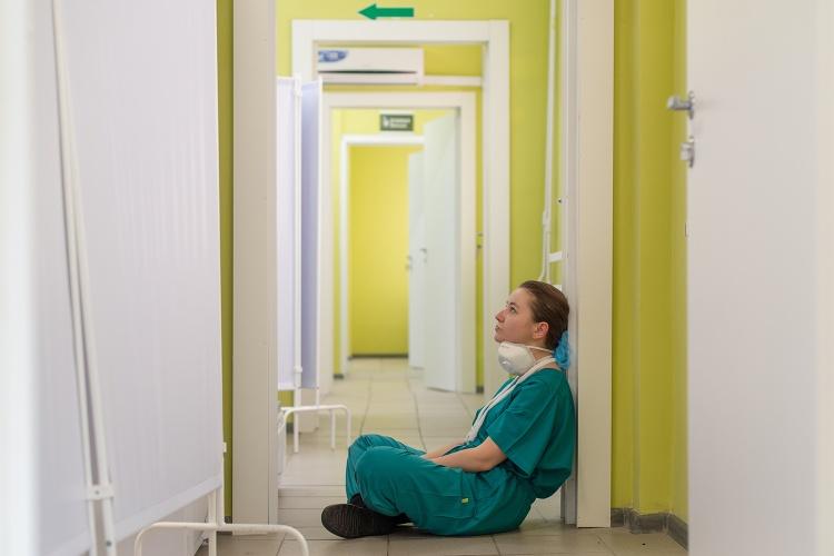Eine erschöpfte Pflegekraft sitzt auf dem Fussboden
