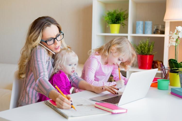 Mutter arbeitet in der Küche am Laptop mit zwei kleinen Kindern (Foto: Shutterstock)