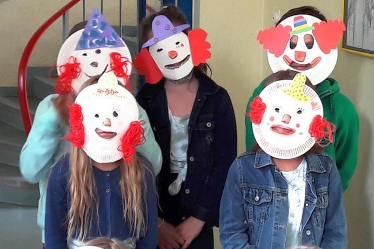 Kinder mit Clownsmasken beim Zirkusprojekt der Stadtranderholung Lippstadt (Foto: Diakonie Ruhr-Hellweg)