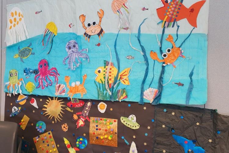 Kinder haben bunte Krabben und Fische als Wanddekoration gebastelt.