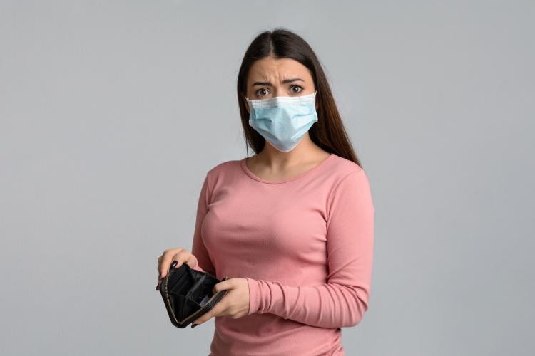 Frau mit Maske und leerem Portemonnaie (Foto: Shutterstock)