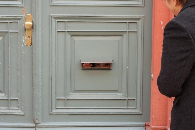 Nähe auf Distanz: Eine Frau unterhält sich mit einem Kind durch den Briefkastenschlitz.