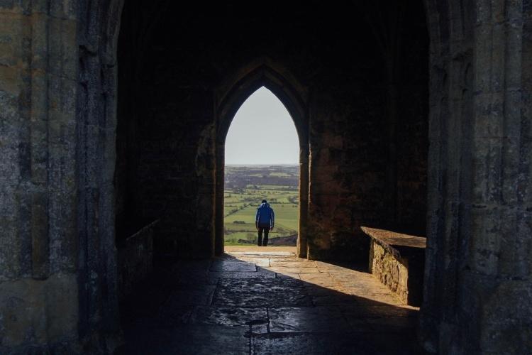 Ein Mann tritt aus einer dunklen Kirche ins Licht (Foto: pixabay.de)