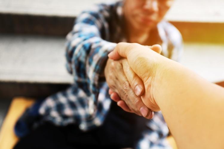 Einem Obdachlosen wird die Hand gereicht. (Foto: Shutterstock)