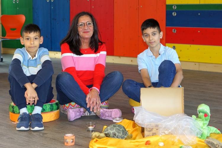Selim und Yasin sitzen mit Hospizhelferin Birgit Prottung vor der Schatzkiste am Boden.