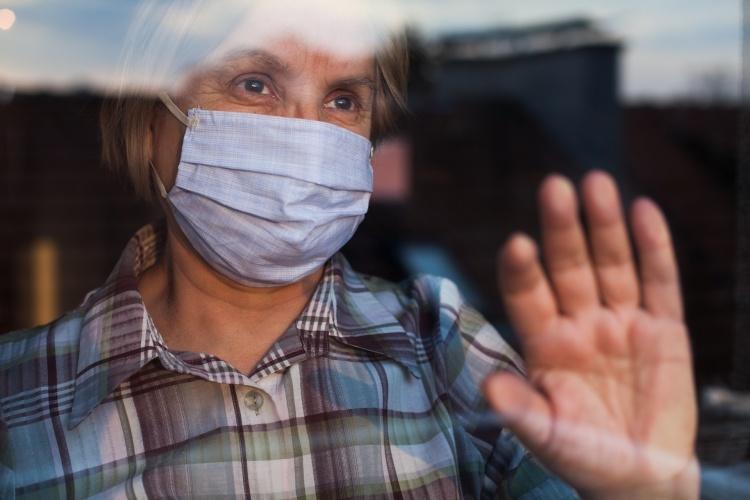 Ältere Frau mit Maske steht am Klinikfenster (Foto: Shutterstock)