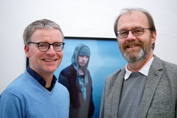 Martin Treichel und Jürgen Hass von der Männerarbeit der westfälischen Kirche vor dem Foto eines jungen Mannes