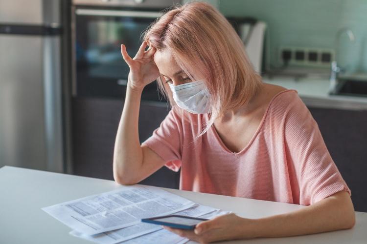 Junge Frau mit Maske sitzt verzweifelt vor Papieren