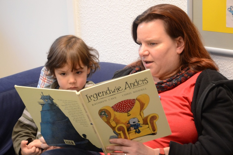 Eine Erzieherin in der Kita der Diakonie Düsseldorf liest einem Jungen vor.