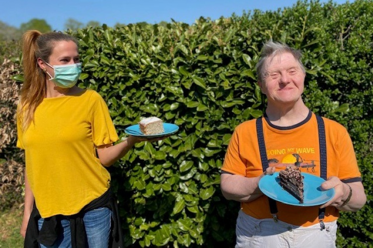 Bewohner eines Wohnheims für Menschen mit Behinderung und seine Betreuerin mit einem Stück Kuchen (Foto: Diakonisches Werk im Kirchenkreis Recklinghausen)
