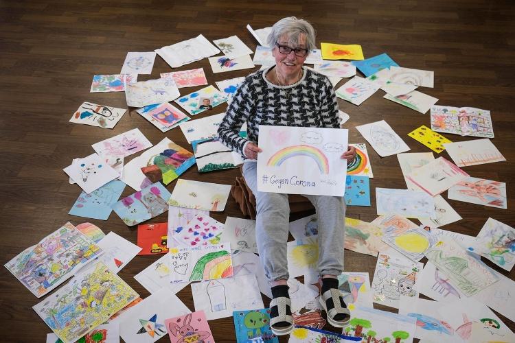 Zusammenhalt: Kinder aus der Kita Friedenskirche in Witten-Annen haben für die Senioren gemalt. Maria Flick vom Altenzentrum am Schwesternpark Feierabendhäuser der Diakonie Ruhr präsentiert die Bilder. (Foto: Diakonie Ruhr/ Vincke)