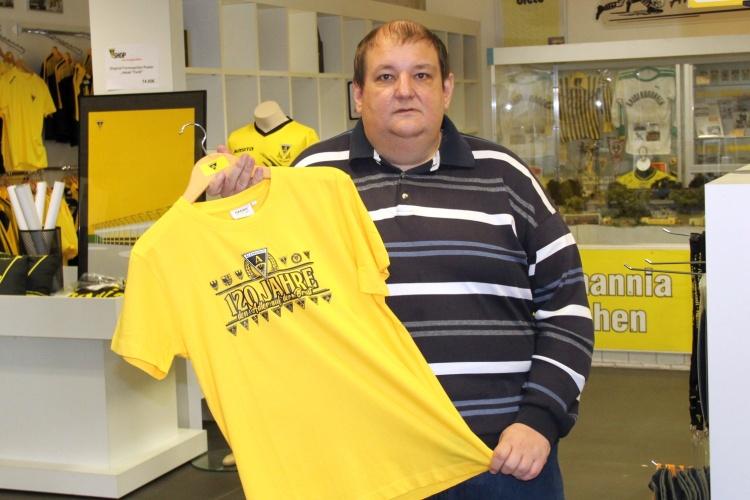 Markus Mingers zeigt ein T-Shirt im Alemannia Aachen-Shop des diakonischen Beschäftigungsträgers WABe (Foto WABe)