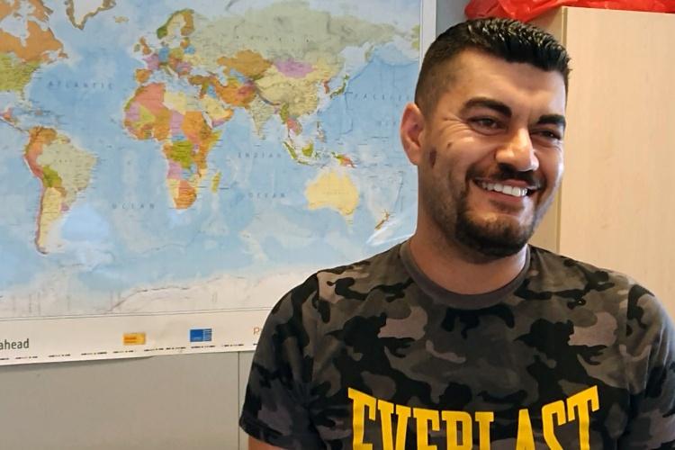 Der Iraker Tahssen Elias steht vor einer Weltkarte im Gruppenraum der Flüchtlingsunterkunft.