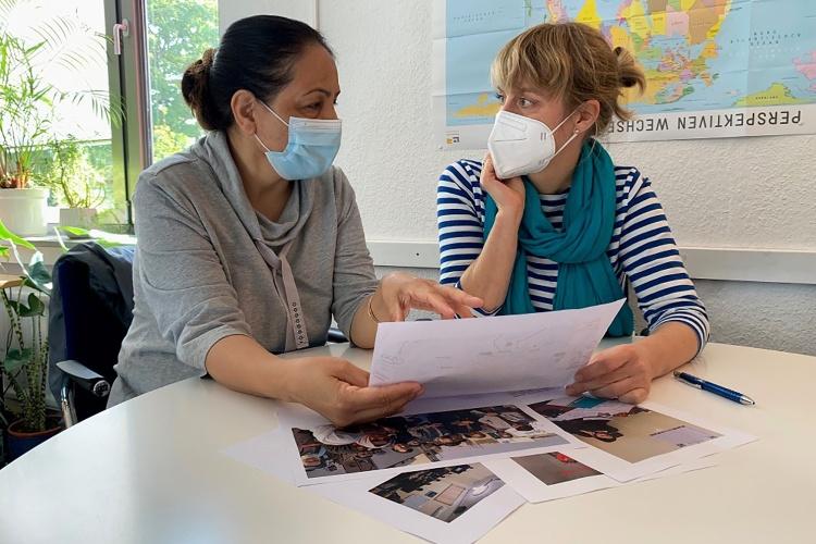 Flüchtlingsberatung: Zwei Frauen sitzen mit Maske am Tisch