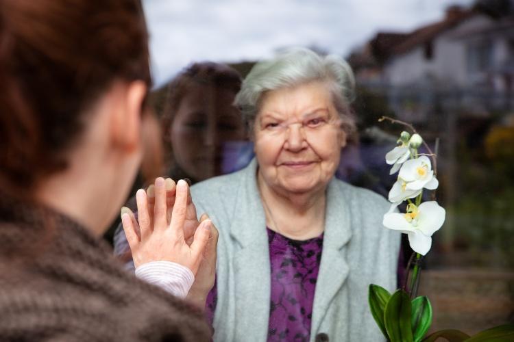 Besuchsverbote: Seniorin und Enkelin halten Hände an einer Plexiglasscheibe (Foto: Shutterstock)