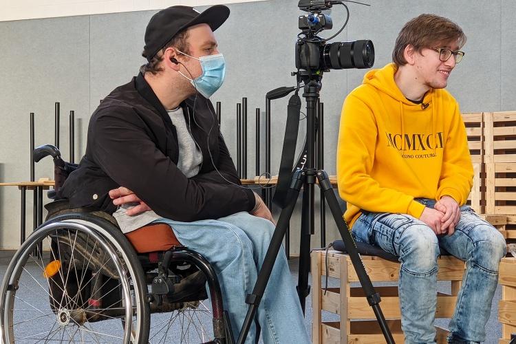 Kameramann Simon Roehlen (links) und Interviewer Philipp Fuchs sitzen konzentriert in einer Turnhalle während eines Drehs.