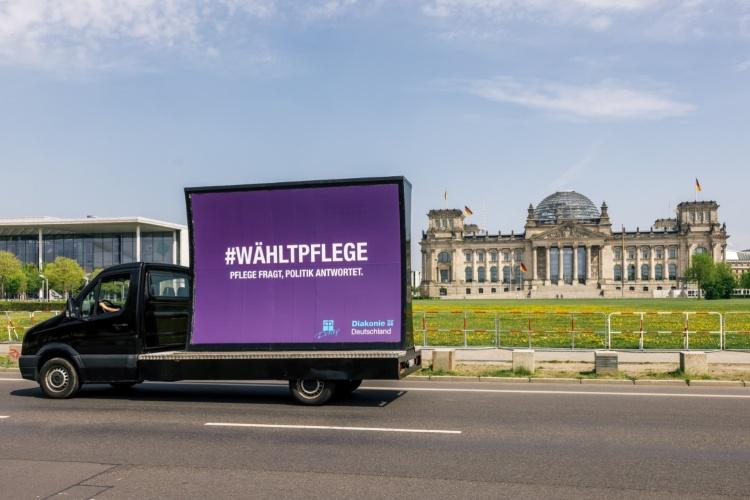 """Diakonie-Wagen mit Logo """"Wählt Pflege"""" vorm Reichstag in Berlin (Foto: Harms/Diakonie Deutschland)"""