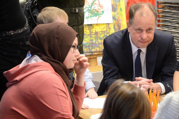 NRW-Familienminister Joachim Stamp unterhält sich mit einer Erzieherin und Kindern in der Kita der Diakonie Düsseldorf.