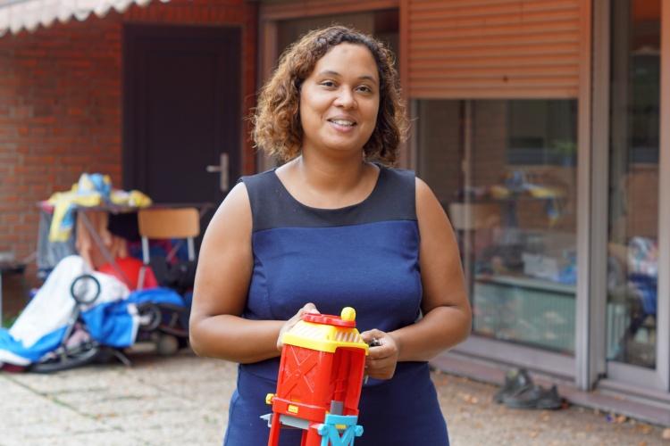 Diakonie-Sozialarbeiterin Sheba Shumpert mit einem Kind im Garten der Notunterkunft für Familien in Köln