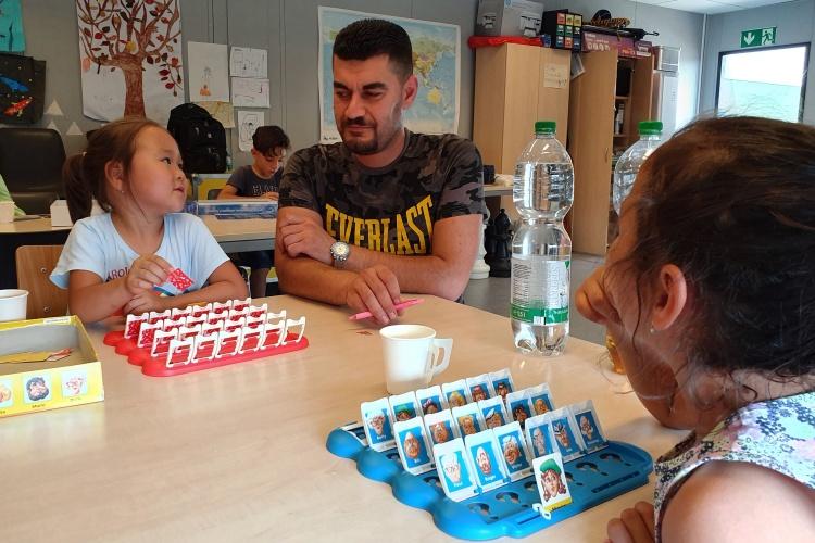 Der Iraker Tahssen Elias erklärt zwei Mädchen ein Spiel.