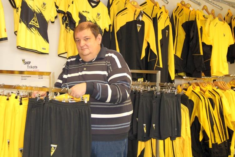 Markus Mingers vor den Kleiderständern im Alemannia Aachen-Shop des diakonischen Beschäftigungsträgers WABe (Foto WABe)