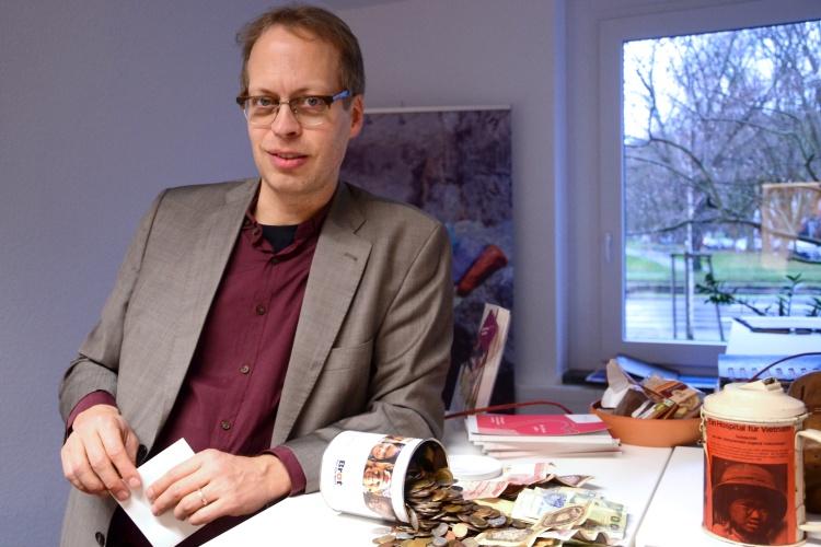 Diakonie RWL-Fundraiser Ulrich Christenn in seinem Büro vor einer ausgekippten Spendendose