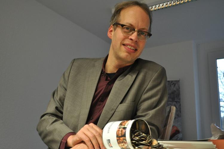 Diakonie RWL-Fundraiser Ulrich Christenn mit einer Sammeldose in seinem Büro
