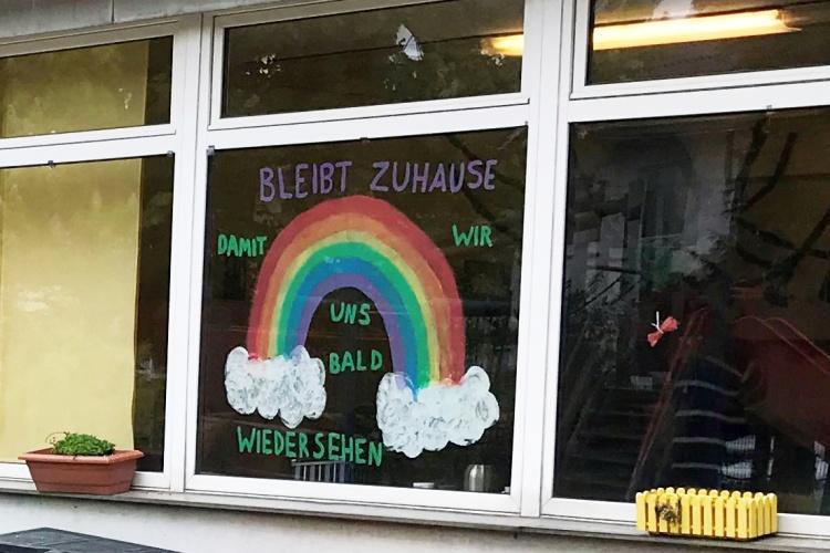 Regenbogen mit einer klaren Botschaft: Bleibt zuhause, damit wir uns bald wiedersehen. (Foto: Kita Helmertweg)