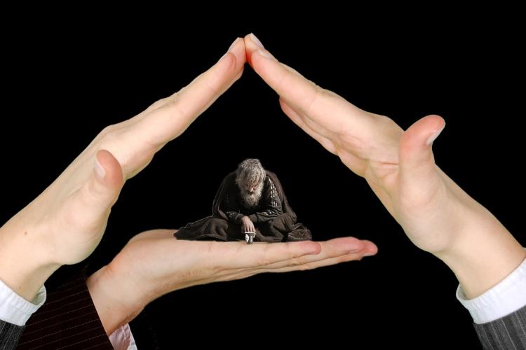 Themenfoto Obdachloser mit Händen, die ihn schützen (Foto: pixabay.de)