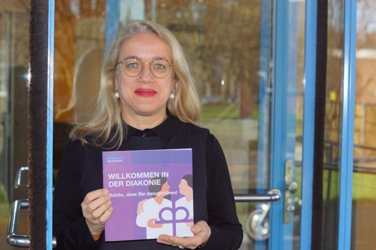 Neue Mitarbeitende willkommen heißen: Barbara Montag präsentiert die neue Broschüre der Diakonie.