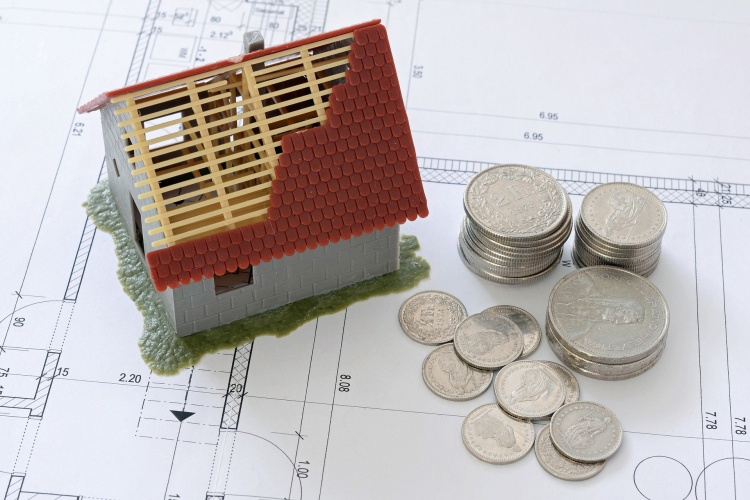 Unfertiges Modellhaus steht auf einem Bauplan. Daneben liegen Münzen