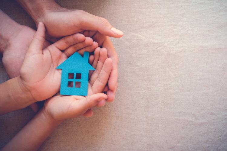 Kinder- und Erwachsenenhände halten ein Haus aus Papier (Foto: Shutterstock)